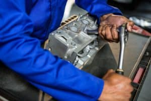 Mechanic repairing engine part with ratchet at the repair garage